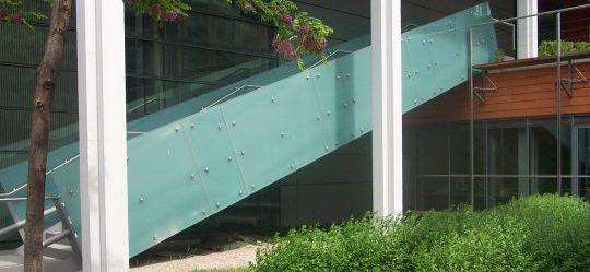 Treppe mit Glasgeländer und gebogenem Edelstahl- Handlauf