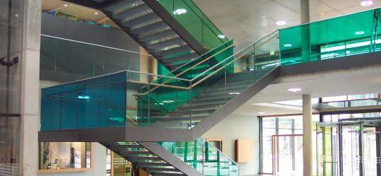 Treppe als  Stahlkonstuktion mit farbigen Ganzglas Geländer, sowie kombinierten Holz - Edelstahl- Handläufen